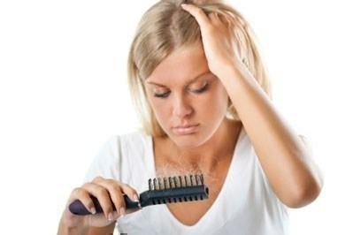 Woman looking at her hairbrush
