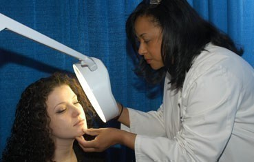 A dermatologist examines a young woman at a skin cancer screening