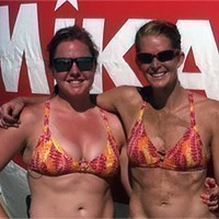 two beach volleyball players standing and posing for a picture outside