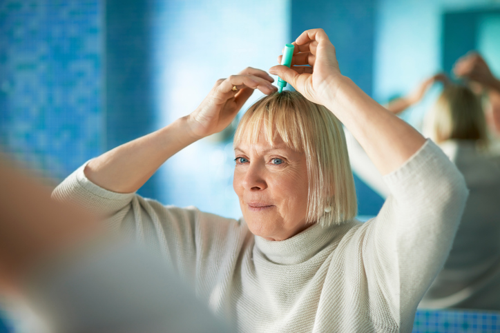 Woman-applying-medicine-to-scalp.jpg