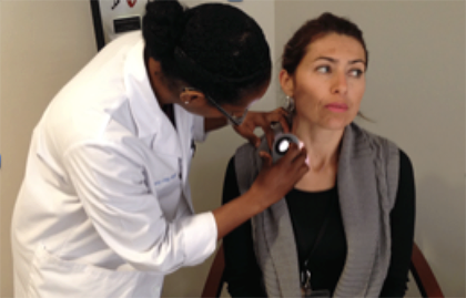 Dermatologist examines woman during a free skin cancer screening.