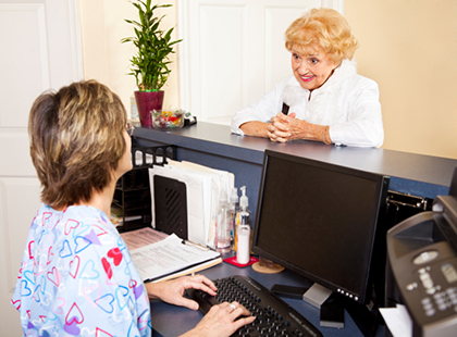 Senior woman standing at the reception desk in a medical office