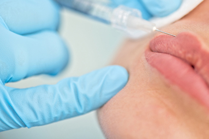 Dermatologist injects filler into lip